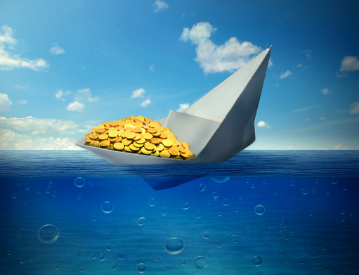 sinking paper boat transporting gold symbol of declining commodity prices